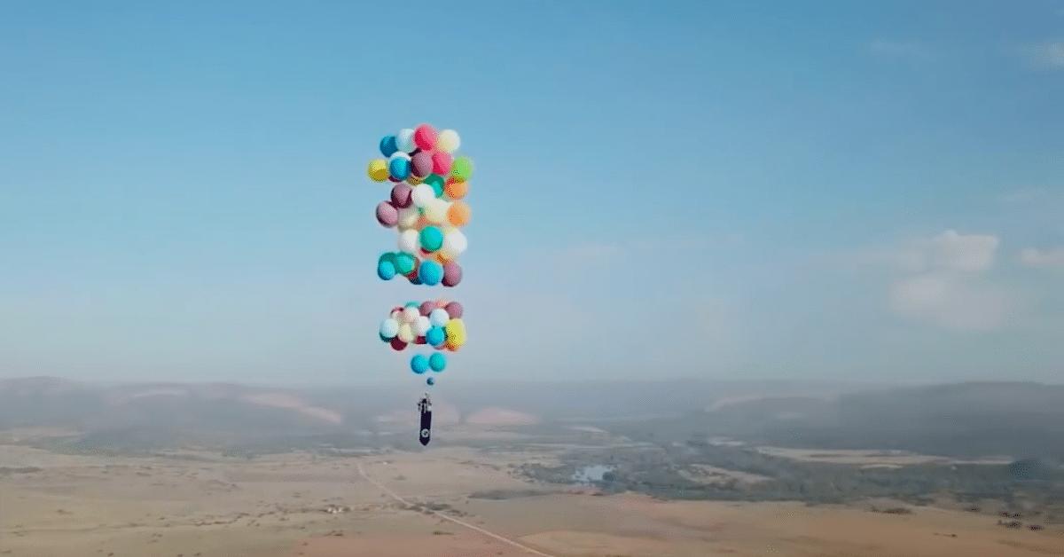 Mies lentää ilmojen halki sadan heliumpallon varassa