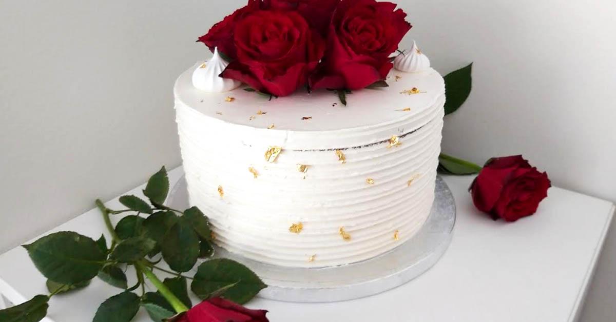 Valkoinen kreemikakku ruusuilla – sisällä mustikka- ja tummasuklaamoussea